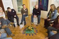 Eltern und Pädagogen sitzen in einem Sitzkreis, i
