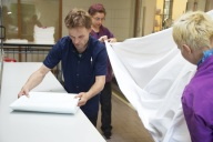 Bild Drei Mitarbeitende mit Handicap legen Wäsche