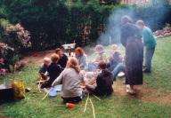 Eine Jugendgruppe sitzt um eine Feuerstelle und gr