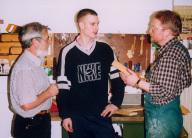 1 Teenager steht mit Betreuer in einer Werkstatt b
