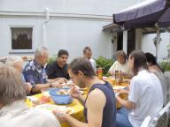8-10 Männer sitzen um einen Tisch und nehmen eine