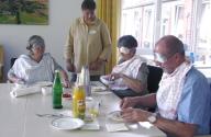Bild: Eine Frau steht an einem Tisch. Drei Mensche