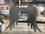 Auf dem Bild sieht man Engelsflügel aus Metall an einer Vorrichtung zum Pulvern hängen.