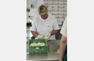 eine Mitarbeiterin schält Gemüsezwiebeln