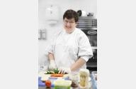 Junge Frau schneidet auf einem Küchenbrett mit ei