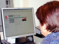 Frau sitzt vor Computermonitor und blickt auf das Web-Tagebuch