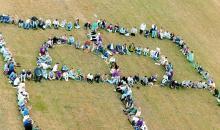 Menschen bilden ein Kronenkreuz auf dem Rasen