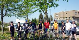 10 Mitarbeiter in bunten Fahrradtrikots mit Ihren Rädern vor dem ersten Training.