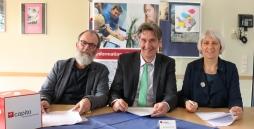 Stephan Bruns, Jan-Henrik Schmidt und Magdalena Schwering unterschreiben die Qualitätspartnerschaft.