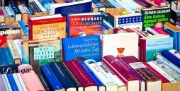 Viele verschiedene Bücher werden am Flohmarktstand präsentiert und ausgelegt.