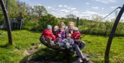 Bild: Zwei Frauen sitzen mit fünf Kindern auf einer großen Schaukel. Sie lächeln in die Kamera.