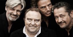 Vier Männer vor schwarzem Hintergrund lächeln in die Kamera