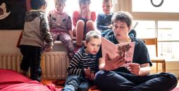 Bild: Ein Mitarbeiter der Kindertagesstätte Nortorf liest fünf Kindern aus einem Buch vor.