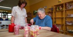 Das Bild zeigt eine Mitarbeiterin und deren Betreuerin der Lern- und Motivationsgruppe bei der hauseigenen Kerzenherstellung.