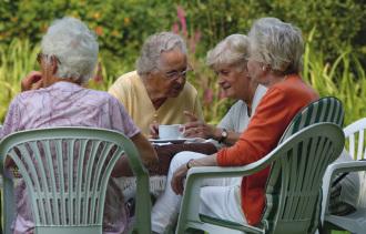 Vier alte Damen sitzen im Garten und trinken Kaffe