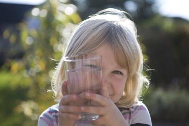 Ein Kind hält ein Glas Wasser in der Hand. Es lä