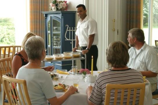 Bild: An einem Tisch sitzen Patienten in unserem Lichtdurchfluteten Speisesaal, ein Kellner serviert das Essen.