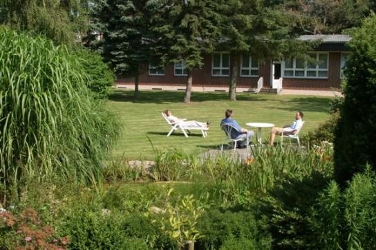 Bild: Eine Wiese an einem Teich gelegen mit verschiedenen Sitz- und Liegemöglichkeiten