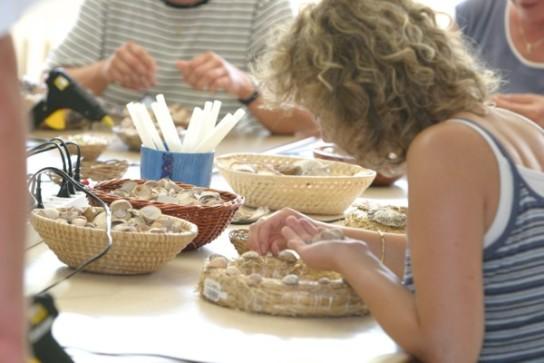 Bild: Eine Frau beklebt einen Kranz mit Muscheln im Kreativbereich des Marienhofs