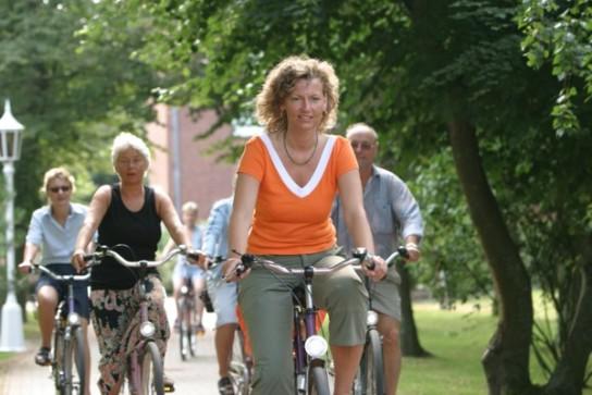 Bild: Eine Frau fährt auf dem Fahrrad, im Hintergrund weitere Fahrradfahrer