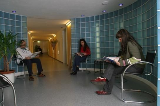 Bild: Personen lesen im Wartebereich zur Bäderabteilung
