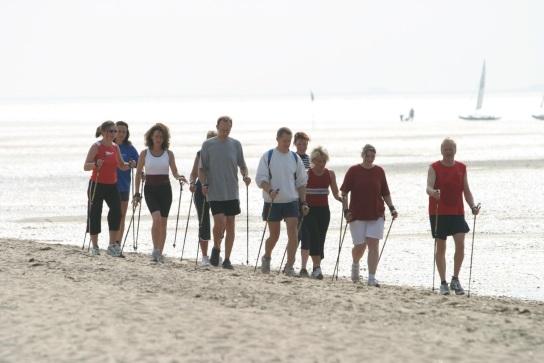Bild: Eine Nordic Walking Gruppe am Strand, im Hintergrund sind Segelboote auf dem Wasser