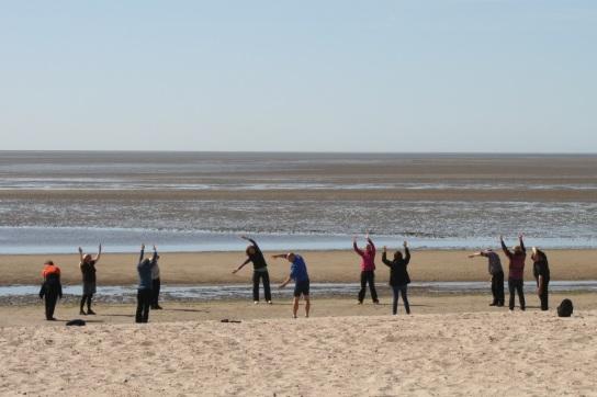 Eine Gruppe Patienten macht Atemtherapie am Strand, im Hintergrund Watt
