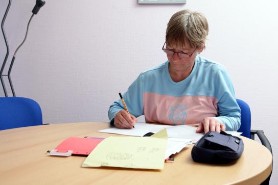 Eine Mitarbeiterin sitzt an einem Tisch und schrei
