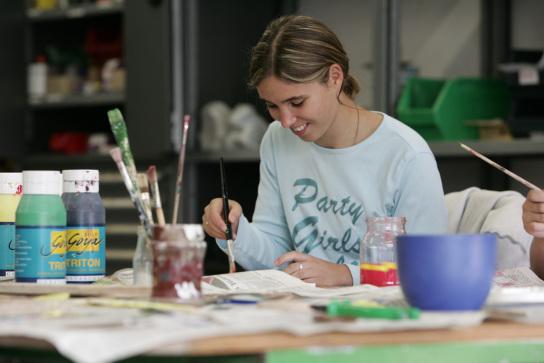 Eine Mitarbeiterin mit Pinsel in der Hand am Arbei