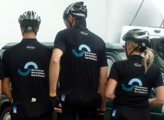 Rückansicht von drei Mitarbeitern in Fahrradtrikots mit dem Firmenlogo der Stormarner Werkstätten Bad Oldesloe auf dem Rücken.