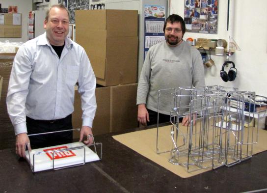 Ein Mitarbeiter mit Handicap zeigt dem Kollegen der Camfil KG die Montagearbeit.