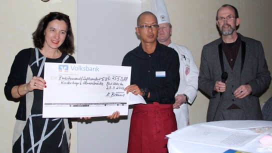 Kim Arnhold übergibt den symbolischen Scheck an die Leiterin des Kinderhospizes.
