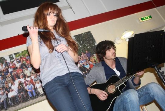 Eine Sängerin und ein Gitarrist auf der Bühne.