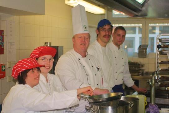 Fünf Mitarbeiter der Küchengruppe präsentieren sich bei der zubereitung der Speisen.