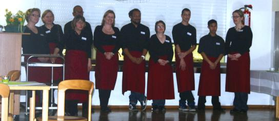 Zehn Servicekräfte nach getaner Arbeit in schwarzer Kleidung mit roten Schürzen.