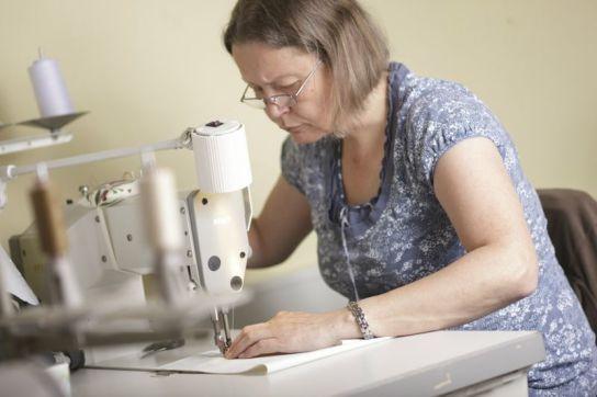 Eine Frau bedient eine Tischnähmaschine