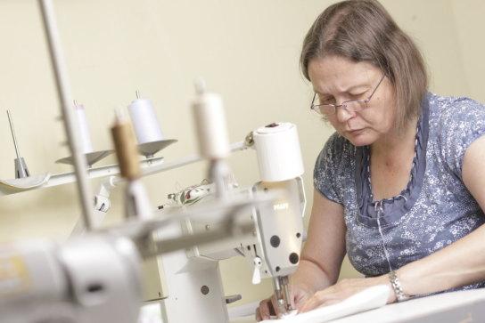 Eine Mitarbeiterin an der Tischnähmaschine