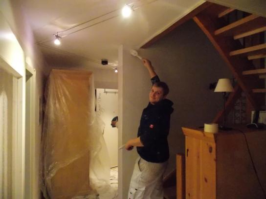 Ein Malergeselle streicht eine Wand