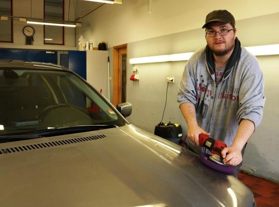 Ein Mitarbeitender poliert ein Auto