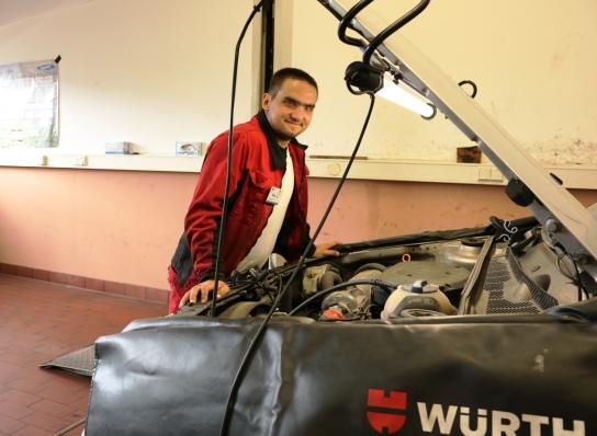 Ein Mitarbeitender inspiziert einen Motor