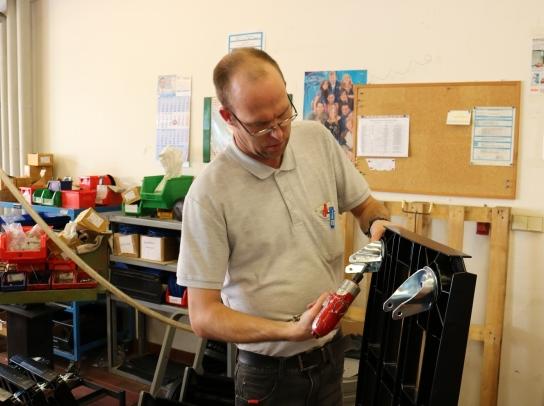 Ein Mitarbeitender schraubt Teile zusammen