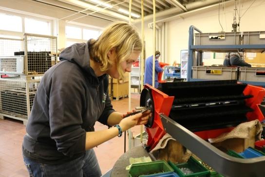 Eine Mitarbeitende montiert einen Kehrwagen.
