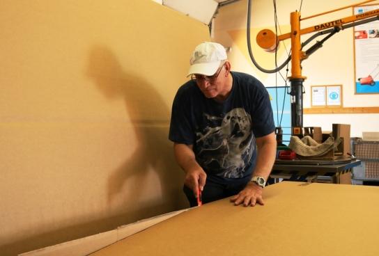 Ein Mitarbeitender schneidet Pappe