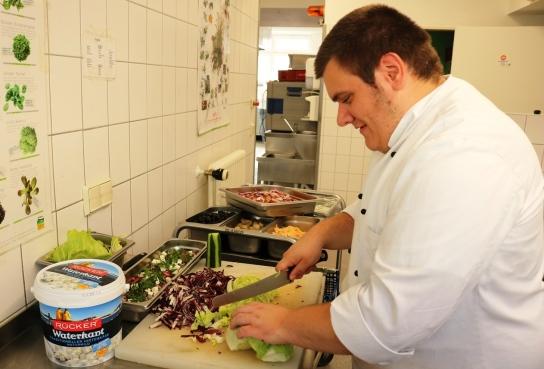 Ein Mitarbeitender schnippelt Salat