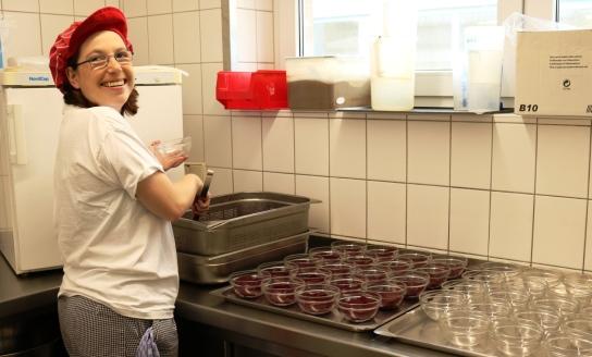 Eine Mitarbeitende verteilt Rote Beete auf Schälc
