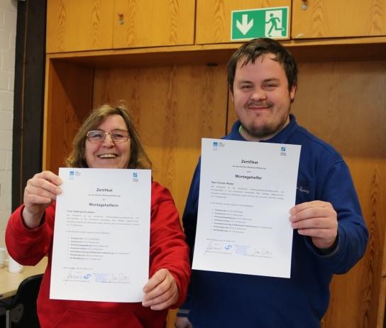 Zwei Mitarbeitende mit Handicap freuen sich über