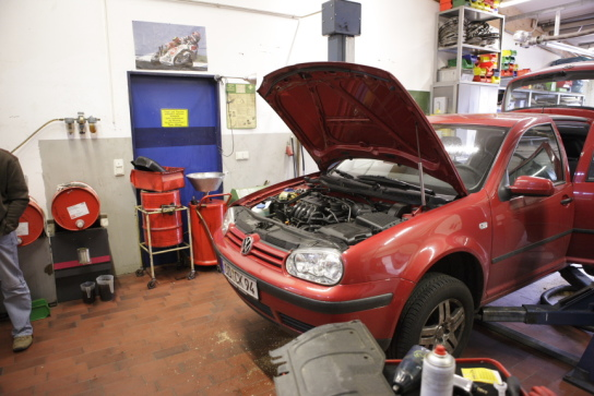 ein Auto mit offener Motorhaube in der KFZ-Werksta