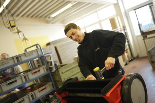 ein Mitarbeiter bei der Montage einer Kehrmaschine