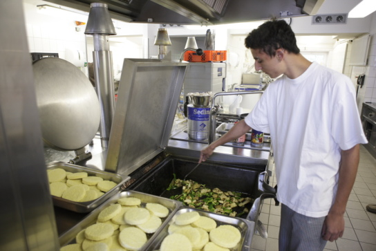 ein Mitarbeiter in der Küche brät Gemüse an