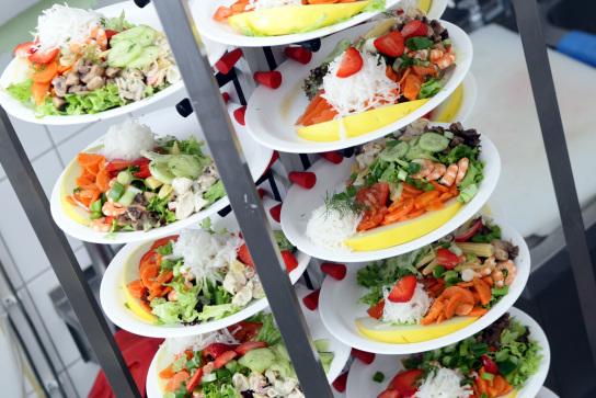 Neun bunte Teller mit frisch zubereitetem Salat.